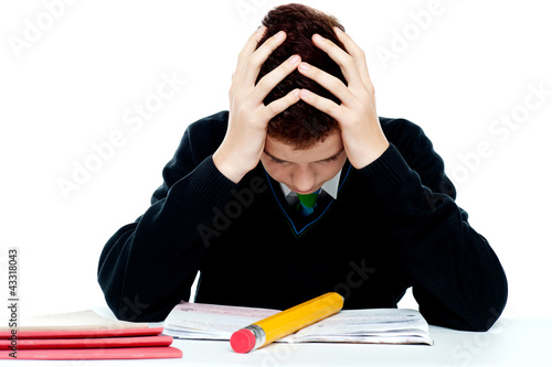 Confused student holding his head in classroom
