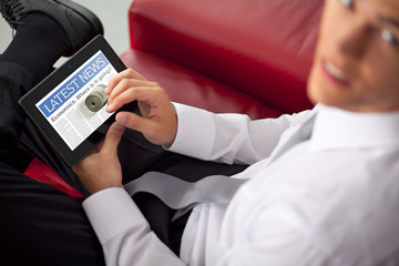 Young businessman holding and touching a digital tablet