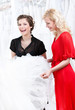 Two girls discuss the wedding dress hesitating about fitting