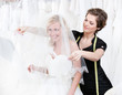 Shop assistant sets the veil of the bride, white background