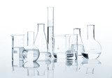 Set of classic laboratory flasks with a clear liquid, isolated