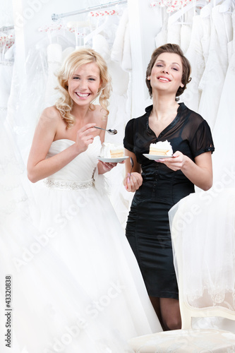 Laughing shop assistant and the bride eat a delicious cake