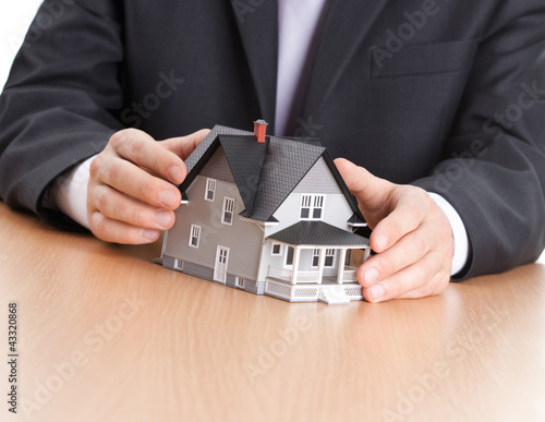 Real estate concept - businessman hands architectural model