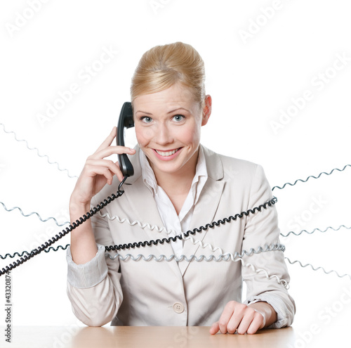 Young businesswoman sitting at a table tied with phone wire