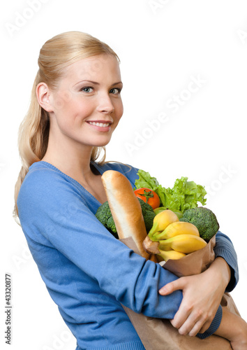 Beautiful woman with a paper bag full of healthy food