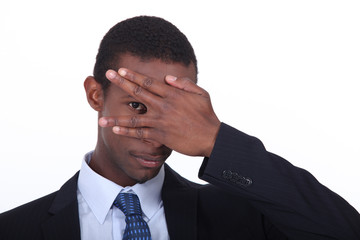 Businessman covering face with hand