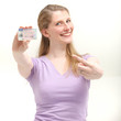 Smiling blonde woman pointing on her ID card