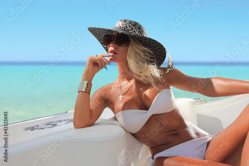 Sexy woman with hat on a luxury yach