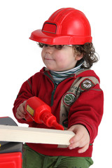 Little boy with toy drill pretending to be workman