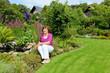 Seniorin sitzt am Teich im Garten
