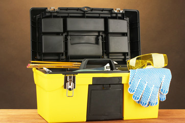 Open yellow tool box with tools  on brown background close-up