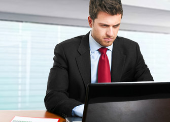 Thoughtful businessman in front of his laptop