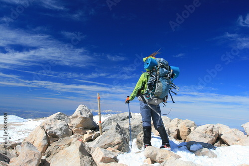 Woman with backpack on top of mountain