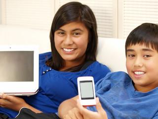 kinder zeigt mobiltelefon und computer