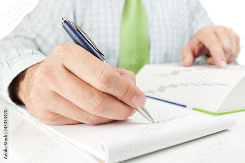 "Businessman writing word ""INFLATION"" in notepad."