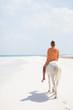 Caucasian woman riding on horseback on beach