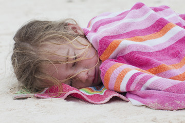 Caucasian girl wrapped in a towel sleeping on beach