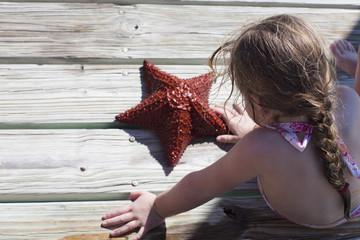 Caucasian girl sitting on dock looking at starfish