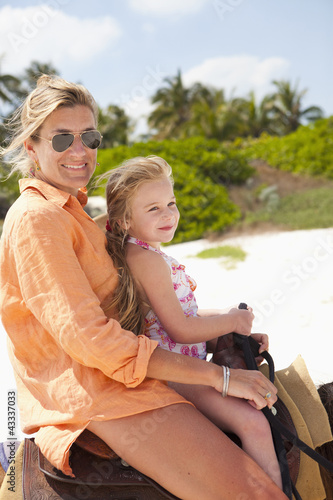Caucasian mother and daughter riding on horseback