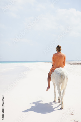 Caucasian woman riding on horseback on beach
