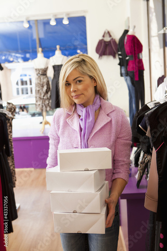 Hispanic business owner carrying boxes in store