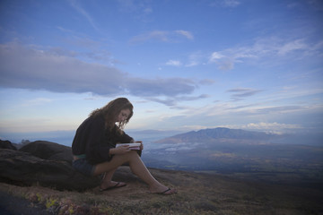 Mixed race woman reading book in hilltop