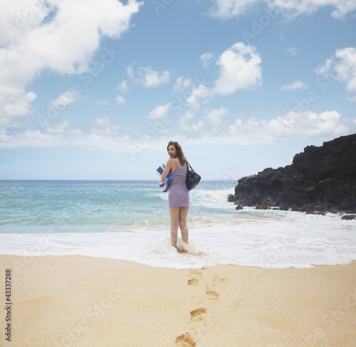 Mixed race woman wading in ocean water