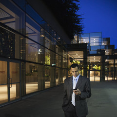 Hispanic businessman using cell phone at night in office courtyard