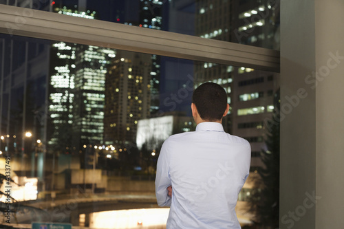 Hispanic businessman looking out office window at night city scene