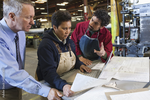 Foreman and workers looking at paperwork in factory