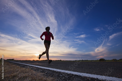 Caucasian runner training on remote road