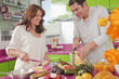 Hispanic couple preparing fruit in kitchen together