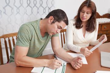 Hispanic couple paying bills together