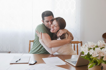 Hispanic couple paying bills and hugging