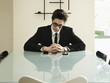 Trendy Caucasian businessman sitting at conference table looking at cell phones