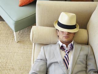 Trendy Caucasian man napping on sofa