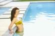 Hispanic woman relaxing in swimming pool