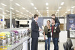 Salesman talking to Hispanic family in appliance department