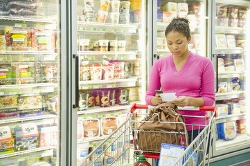 Mixed race woman shopping in frozen food aisle
