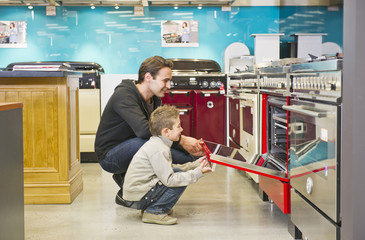 Hispanic father and son looking at stoves