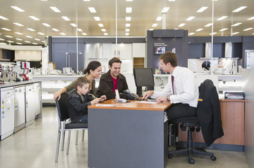 Salesman talking to Hispanic family in home supply store