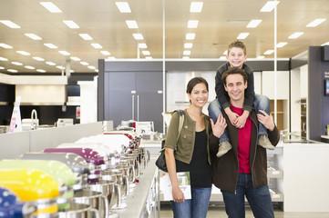 Hispanic family standing in appliance department