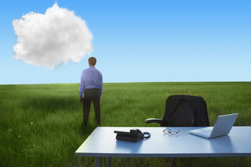 Middle Eastern businessman in field looking at cloud