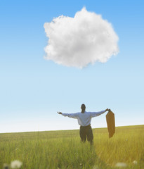 Black businessman in field looking at cloud