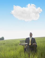 Black businessman sitting at desk in field with laptop