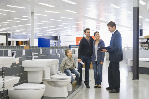 Salesman talking to Hispanic family in bathroom supply store