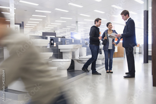 Salesman talking to Hispanic couple in bathroom supply store