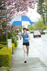 Mixed race runner training on urban sidewalk with umbrella