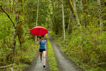 Mixed race runner training on remote road with umbrella