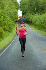 Caucasian athlete running with Olympic torch on remote road